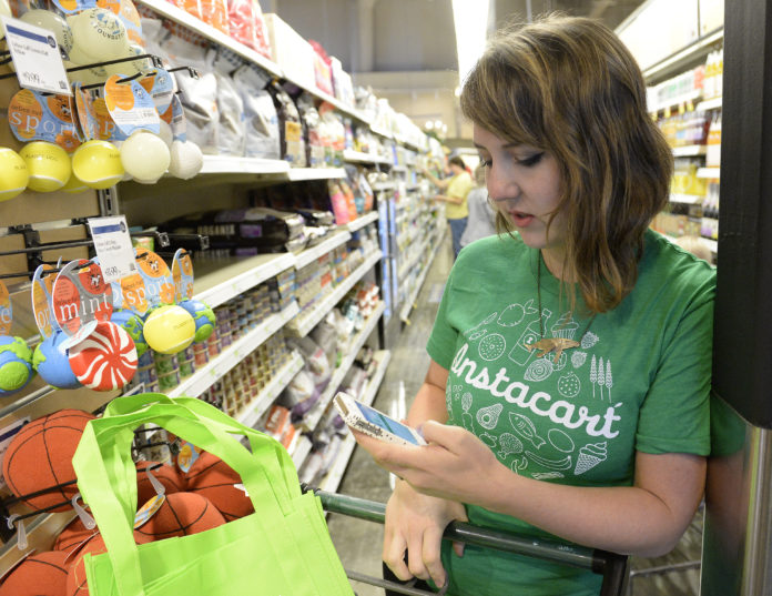 An Instacart shopper checks her phone